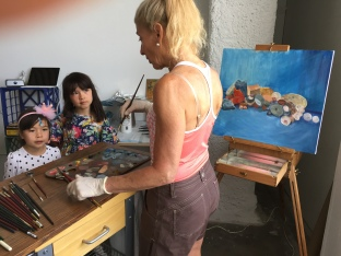Visitors learning from working artist